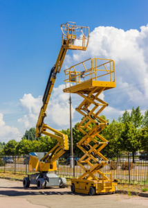 Yellow Scissor lift and articulated boom lift with fence and green trees in background
