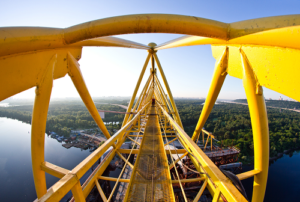 Arial view of a yellow boom lift with water and land below
