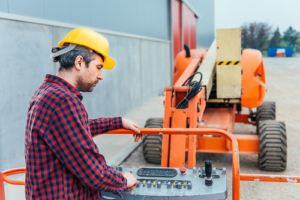 worker wearing yellow helmet standing inside boom lift