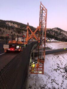 Orange Bridge inspection truck placed at side of bridge